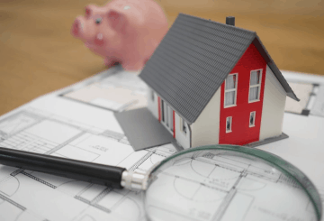 Model home, piggy bank, and magnifying glass sit atop a blueprint